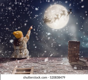 Merry Christmas and happy holidays! Cute little child girl sitting on the roof and looking at Santa Claus flying in his sleigh against moon sky. Kid enjoy the holiday. Christmas legend concept.