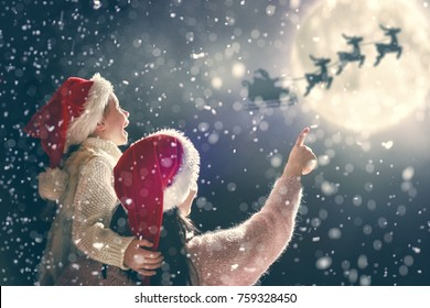 Merry Christmas and happy holidays! Cute little child with mother. Santa Claus flying in his sleigh against moon sky. Family enjoying the holiday on dark background.