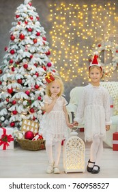 Merry Christmas and Happy Holidays Cute little child girls decorating the white green Christmas tree indoors with alot of presents wearing evening dresses with beautiful faces.
