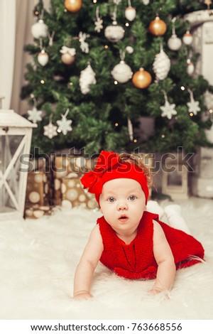 29b17e2c1593 Merry Christmas and Happy Holidays! Cute girl near the Christmas tree  indoors.Cute baby