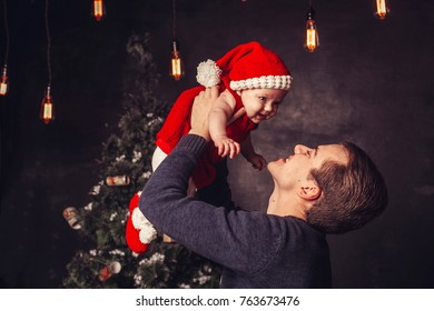 Merry Christmas and Happy Holidays! Dad and daughter near the Christmas tree indoors. The morning before Xmas. Portrait loving family close