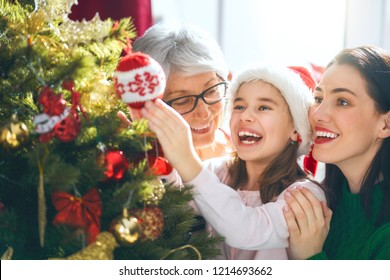Merry Christmas and Happy Holidays! Grandma, mom and daughter decorate the tree indoors. The morning before Xmas. Portrait loving family close up.