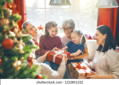 Merry Christmas and Happy Holidays! Grandma, grandpa, mum, dad and child exchanging gifts. Parents and daughter having fun near tree indoors. Loving family with presents in room.
