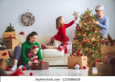 Merry Christmas and Happy Holidays!  Grandmother, mother and child decorating the tree in room. Loving family indoors.