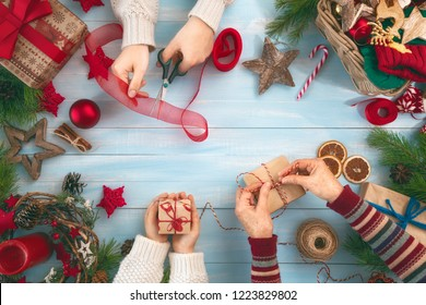 Merry Christmas and Happy Holidays! Grandmother, mother and daughter prepare gifts. Baubles, presents, candy with ornaments. Top view. Xmas family traditions.