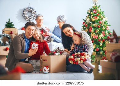 Merry Christmas and Happy Holidays!  Grandparents, mother, father and children decorate the tree in room. Loving family indoors.