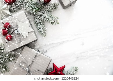 Merry Christmas and Happy Holidays greeting card, frame, banner. New Year. Christmas silver handmade gift boxes on white marble background top view. Winter holiday theme. Flat lay.