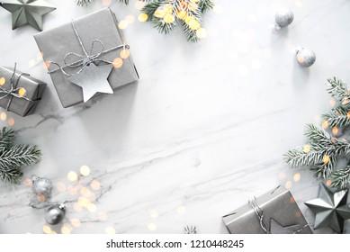 Frohe Weihnachten und Fröhliche Feiertage Grußkarte, Rahmen, Banner. Neujahr.Weihnachtssilber handgefertigte Geschenkbox auf weißem Marmor Hintergrund Draufsicht. Winterurlaub-Thema. Flat lay.