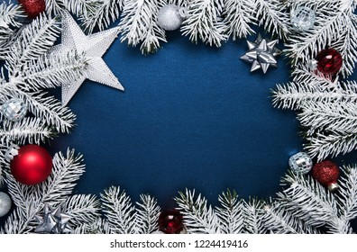 Merry Christmas and Happy Holidays greeting card, frame, banner. New Year. Noel. Christmas ornaments and fir tree on blue background top view. Winter holiday theme. Flat lay.