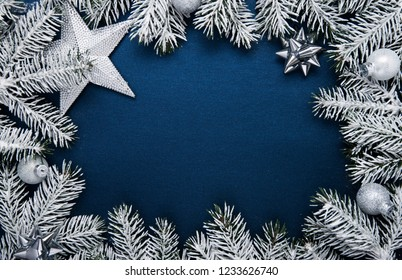 Merry Christmas and Happy Holidays greeting card, frame, banner. New Year. Noel. Christmas ornaments and fir tree on blue background top view. Winter holiday xmas theme. Flat lay.