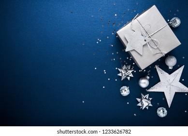 Frohe Weihnachten und Fröhliche Feiertage Grußkarte, Rahmen, Banner. Neujahr. Noel. Silberne Weihnachtsgeschenke, Ornamente auf blauem Hintergrund, Draufsicht. Winterurlaub Weihnachten Thema.Flat lay.