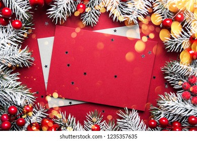 Merry Christmas and Happy Holidays greeting card, frame, banner. New Year. Noel. Silver, white and red Christmas ornaments and fir tree on red background top view. Winter holiday xmas theme. Envelope.
