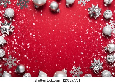 Merry Christmas and Happy Holidays greeting card, frame, banner. New Year. Noel. Christmas white and silver ornaments on red background top view. Winter holiday xmas theme. Flat lay.