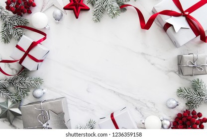 Merry Christmas and Happy Holidays greeting card, frame, banner. New Year. Red, silver Christmas gifts, presents and ornaments on white marble background top view. Winter holiday xmas theme. Noel. Fla