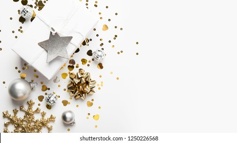 Merry Christmas and Happy Holidays greeting card, frame, banner. New Year. Christmas golden gifts, presents on white background top view. Winter holiday xmas theme. Noel. Flat lay.
