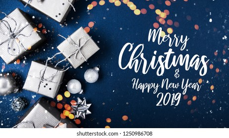 Merry Christmas and Happy Holidays greeting card, frame, banner. New Year. Noel. Silver Christmas gifts, ornaments on blue background top view. Winter holiday xmas theme. Flat lay.