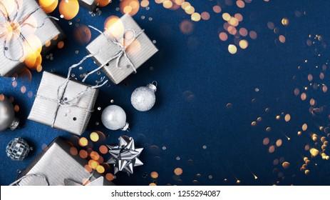 Frohe Weihnachten und Fröhliche Feiertage Grußkarte, Rahmen, Banner. Neujahr. Noel. Silberne Weihnachtsgeschenke, Ornamente auf blauem Hintergrund, Draufsicht. Winterurlaub Weihnachten Thema. Flat lay.