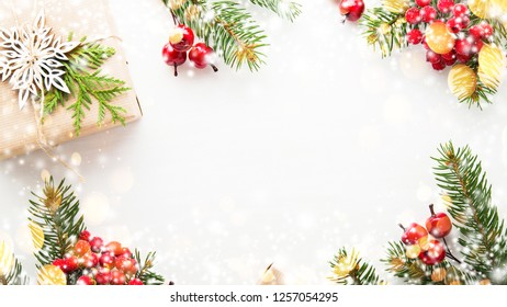 Merry Christmas and Happy Holidays greeting card, frame. New Year. Christmas gifts, presents, fir tree and ornaments on white background top view. Winter holiday xmas theme. Noel. Flat lay.