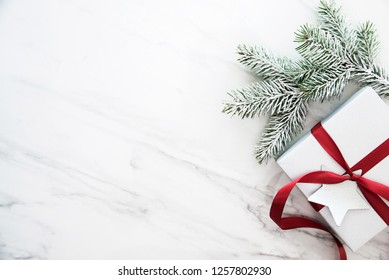 Merry Christmas and Happy Holidays greeting card, frame, banner. New Year. Christmas silver handmade gift boxes on white marble background top view. Winter holiday theme. Noel. Flat lay.