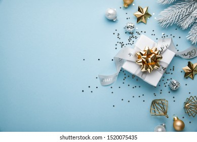Merry Christmas and Happy Holidays greeting card, frame, banner. New Year. Noel. Christmas white, silver and golden ornaments and gift on blue background top view. Winter xmas holiday theme. Flat lay