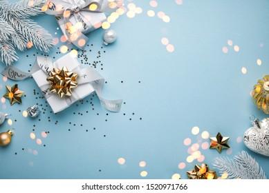 Frohe Weihnachten und Fröhliche Feiertage Grußkarte, Rahmen, Banner. Neujahr. Noel. Weihnachtsweiß, Silber- und Goldene Ornamente und Geschenk auf blauem Hintergrund, Draufsicht. Winterurlaub Thema. Flachlage