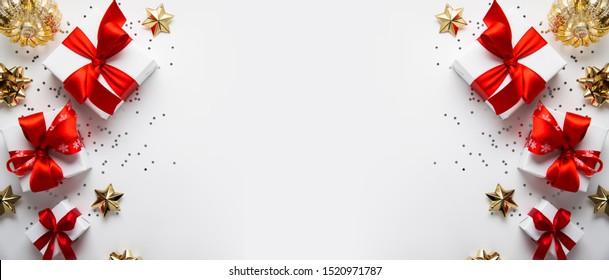Frohe Weihnachten und Fröhliche Feiertage Grußkarte, Rahmen, Banner. Neujahr. Noel. Weihnachtsgeschenke und rote Dekoration auf weißem Hintergrund, Draufsicht. Winterurlaub Thema. Flachlage