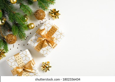 Merry Christmas and happy holidays greeting card, frame, banner. Flat lay Christmas tree fir branch, golden balls, luxury gifts, confetti stars on white background. Winter holiday Xmas theme.