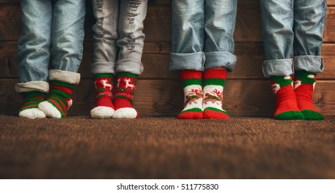 Merry Christmas and Happy Holidays. Group of four kids on wooden background. Children's feet in socks with a Christmas ornament. Red, green and white colors.