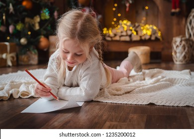 Merry Christmas and Happy Holidays. little child girl writes letter Santa Claus and dreams of a gift background New Year tree indoors.