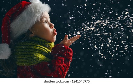 Merry Christmas and happy holidays! Little girl blowing on snow. Child enjoying the game outdoors. Portrait kid on dark background.