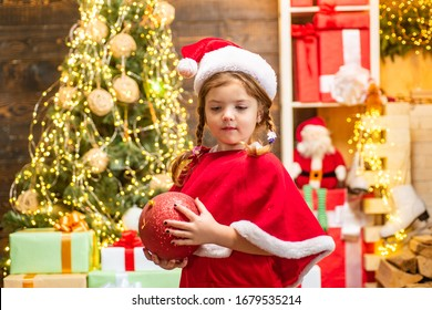 Merry Christmas and Happy Holidays. Little girl in Christmas dress decorating Christmas tree with baubles