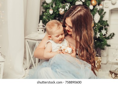 Merry Christmas and Happy Holidays! Mom and daughter near the Christmas tree indoors. The morning before Xmas. Portrait loving family close up.