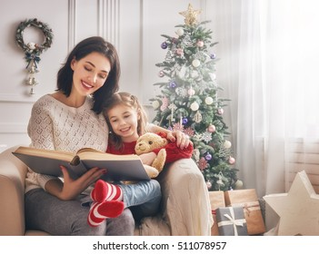 Merry Christmas and Happy Holidays! Pretty young mom reading a book to her cute daughter near Christmas tree indoors.