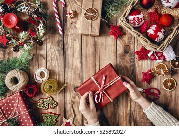 Merry Christmas and Happy Holidays! A woman prepares Xmas gifts. Baubles, presents, candy with christmas ornaments. Top view. Christmas family traditions.