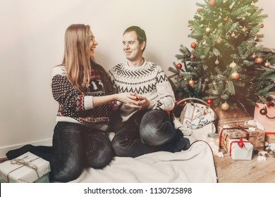 merry christmas and happy new year concept. stylish hipster couple exchanging with gifts in festive room under christmas tree with lights, space for text. happy holidays. family atmospheric moments