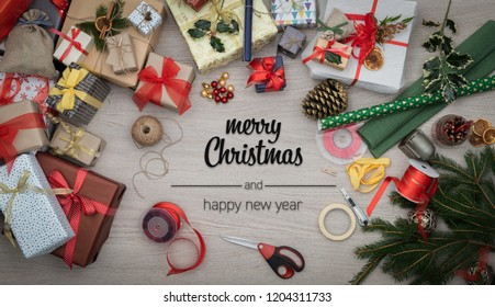Merry Christmas and happy new year greetings in vertical top view wooden table full of christmas gifts presents, pine and handicraft tools.Xmas winter holiday season social media card background
