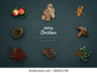 Merry Christmas and happy new year greetings in vertical top view dark blackboard with pomegranate,cinnamon,pine cones,natural concept.Xmas winter holiday season social media card background