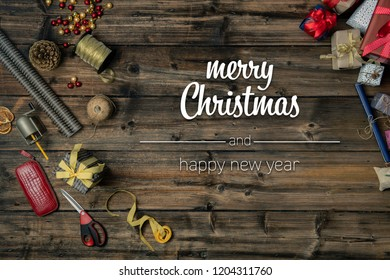 Merry Christmas and happy new year greetings in vertical top view vintage wood.handicraft tools,ribbons,gift present boxes decorated frame.Xmas winter holiday season social media card background