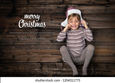 Merry Christmas and happy new year greetings in vertical top view dark vintage wood. Beautiful happy child girl in homewear.Childhood concept.Xmas winter holiday season social media card background