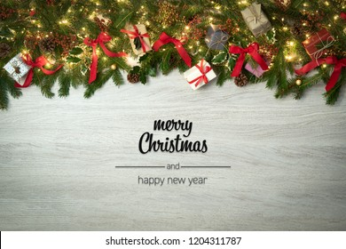Merry Christmas and happy new year greetings in vertical top view white wood with pine branches,ribbons and lights decorated frame.Xmas winter holiday season social media card background