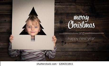 Merry Christmas and happy new year greetings in vertical top view dark vintage wood.Happy child girl in homewear with cardboard tree pine.Childhood concept.Xmas winter holiday season social media card
