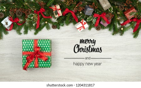 Merry Christmas and happy new year greetings in vertical top view white wood with pine branches,ribbons, lights and gift present box decorated frame.Xmas winter holiday season social media card