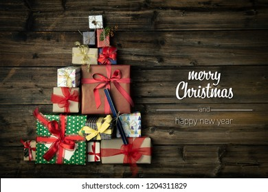 Merry Christmas and happy new year greetings in vertical top view dark vintage wood with christmas tree pine made of gift present boxes.Xmas winter holiday season social media card background
