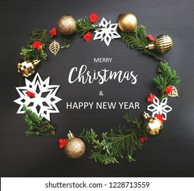 Merry Christmas and Happy New Year background. Xmas Ornaments and text on dark wood.
