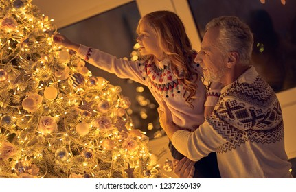 Merry Christmas and Happy New Year! Happy family celebrating winter holiday at home. Grandfather and granddaughter decorating New Year tree.