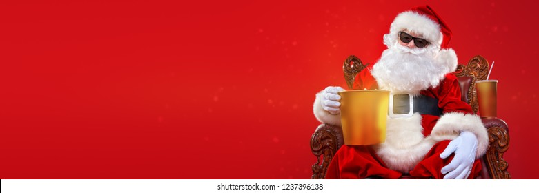 Merry Christmas and Happy New Year. Santa Claus sitting on his armchair and eating popcorn and drinking soda. Entertainment and cinema concept. Red background.