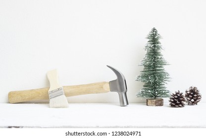 Merry christmas and Happy New year with handy tools background concept, hammers and paintbrush with Christmas tree and pine cones decoration on wood with copy space.