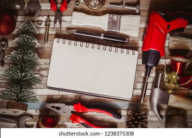 Merry christmas and Happy New year Craftsman Workspace background concept, Variety of handy DIY tools with Christmas ornament decoration. Top view with blank space notebook for your text.