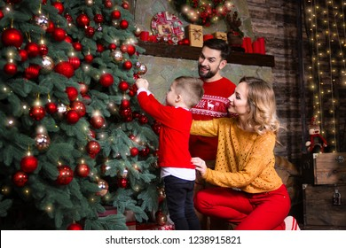 Merry Christmas and Happy New Year concept. Happy family: mother wife woman, father husband man and son boy decorating Christmas tree and preparing celebrating winter holidays at home near fireplace