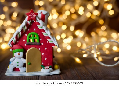 Merry Christmas and happy new year, greeting card. Decorative red toy gingerbread house on a brown background and gold bokeh from a garland.